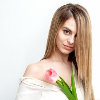 Portrait d'une jeune femme de race blanche heureuse avec une tulipe rose sur un fond blanc avec copie espace