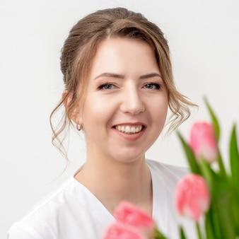 Portrait d'une jeune femme de race blanche heureuse avec des tulipes roses sur fond blanc