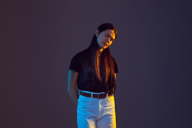 Portrait de jeune femme de race blanche isolé sur fond de studio à la lumière du néon.