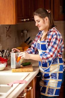 Portrait, de, jeune femme, râper, carotte, sur, cuisine