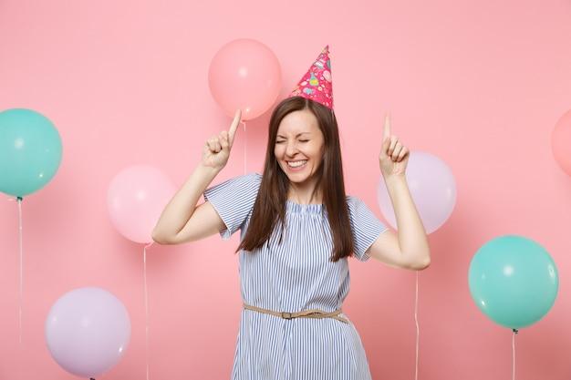 Portrait d'une jeune femme ravie aux yeux fermés en chapeau d'anniversaire et robe bleue pointant l'index vers le haut sur fond rose avec des ballons à air colorés. fête d'anniversaire, émotion sincère des gens.