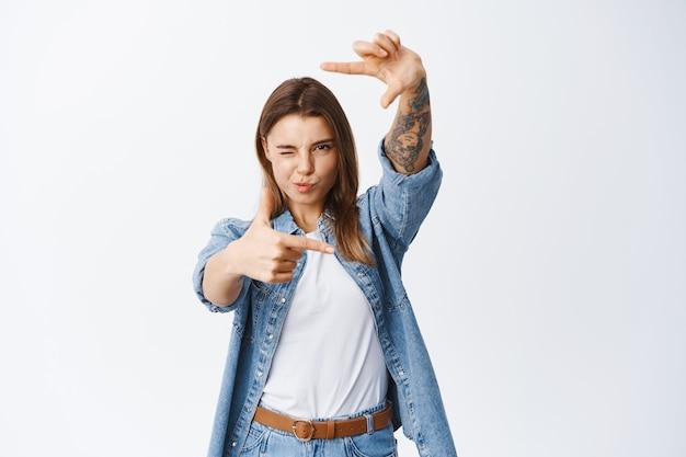 Portrait de jeune femme à la recherche d'un angle parfait, faisant des cadres de doigt et regardant à travers, debout sur un mur blanc