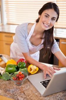 Portrait d'une jeune femme à la recherche d'une recette sur internet