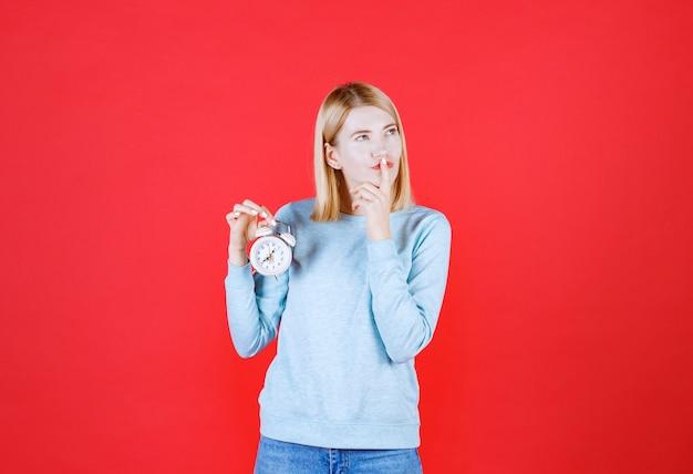 Portrait de jeune femme réfléchie tenant horloge tout en pensant à quelque chose