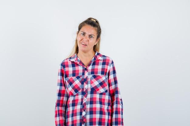 Portrait de jeune femme regardant la caméra en chemise à carreaux et à la vue de face confuse