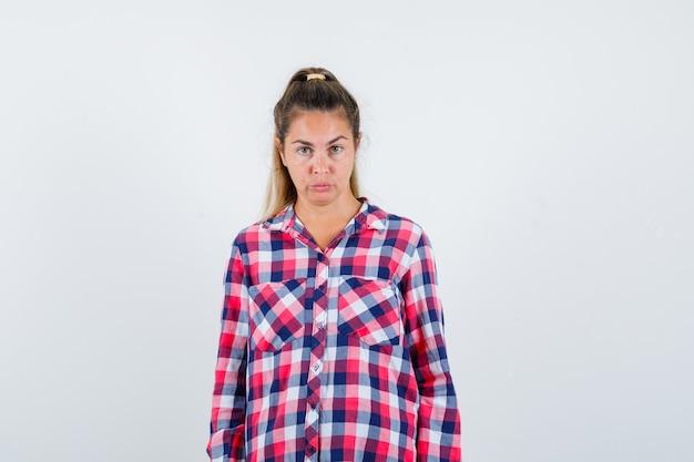 Portrait de jeune femme regardant la caméra en chemise à carreaux et à la vue de face douteuse