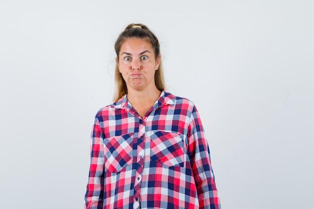 Portrait de jeune femme regardant la caméra en chemise à carreaux et à la vue de face perplexe