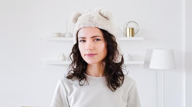 Portrait d'une jeune femme regardant la caméra dans un drôle de chapeau souriant et couchait