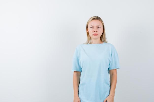 Portrait de jeune femme regardant la caméra en t-shirt et à la nostalgie