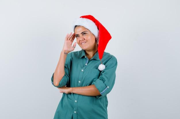 Portrait de jeune femme regardant loin en pensant, mordant la lèvre en chemise, bonnet de noel et regardant la vue de face positive