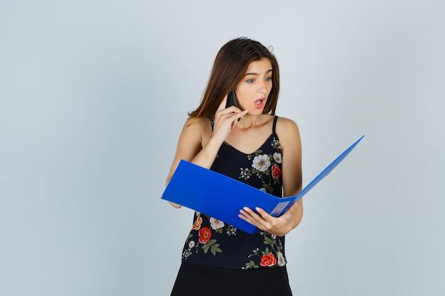 Portrait de jeune femme regardant à travers le dossier tout en parlant au téléphone mobile en blouse et regardant la vue de face choquée