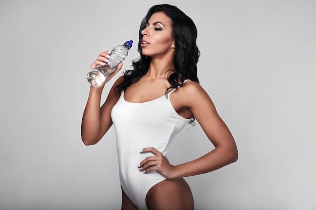 Portrait de jeune femme de remise en forme dans le corps avec une bouteille