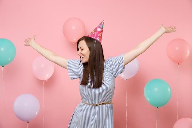 Portrait d'une jeune femme riante aux yeux fermés en chapeau d'anniversaire et robe bleue écartant les mains sur fond rose avec des ballons à air colorés. fête d'anniversaire, concept d'émotions sincères.