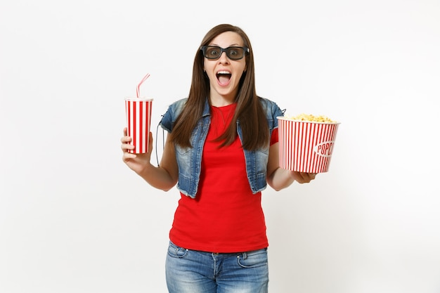 Portrait de jeune femme riante choquée dans des lunettes 3d regardant un film, tenant un seau de pop-corn et une tasse en plastique de soda ou de cola isolé sur fond blanc. émotions dans le concept de cinéma.