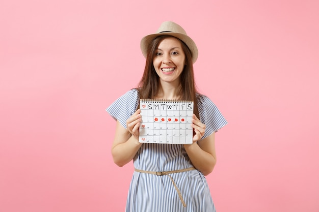 Portrait de jeune femme en robe bleue, chapeau tenant le calendrier des périodes pour vérifier les jours de menstruation isolés sur fond rose tendance brillant. concept médical, sanitaire, gynécologique. espace de copie.