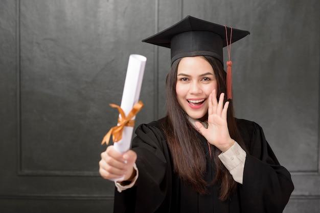 Portrait de jeune femme en robe de graduation souriant et acclamant