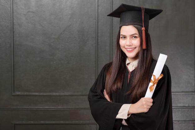 Portrait de jeune femme en robe de graduation souriant et applaudissant sur fond noir