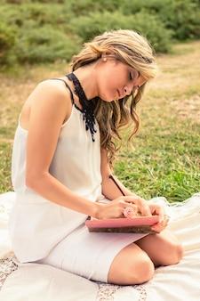 Portrait de jeune femme romantique écrit dans un journal assis sur l'herbe. détendez-vous concept de temps en plein air.