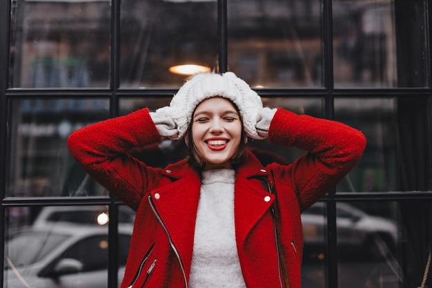 Portrait de jeune femme avec rouge à lèvres et sourire blanc comme neige, vêtue d'un bonnet tricoté blanc et mitaines et veste en laine contre la fenêtre dans un cadre noir.