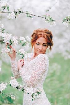 Portrait d'une jeune femme rousse dans un verger de pommiers en fleurs