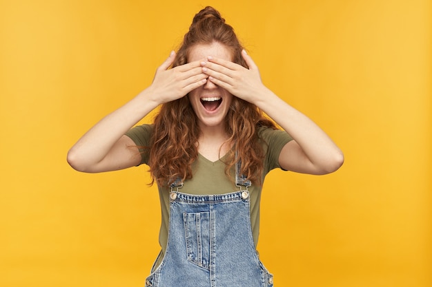 Portrait de jeune femme rousse drôle porte une salopette bleue et un t-shirt vert, sourit largement et ferme les yeux avec ses paumes en attente de surprise. isolé sur mur jaune