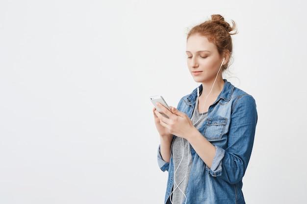 Portrait de jeune femme rousse séduisante calme avec les cheveux peignés en chignon tenant le smartphone et regardant l'écran tout en écoutant de la musique avec des écouteurs