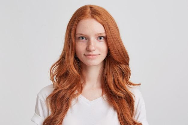 Portrait de jeune femme rousse séduisante souriante aux longs cheveux ondulés