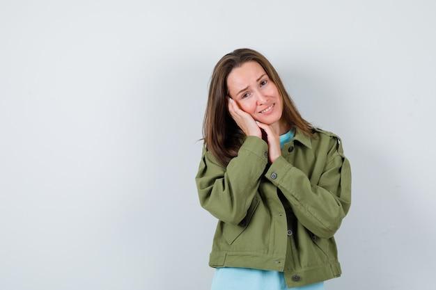 Portrait de jeune femme s'appuyant sur la paume comme oreiller en veste verte et regardant la jolie vue de face