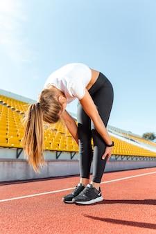 Portrait d'une jeune femme s'échauffant au stade