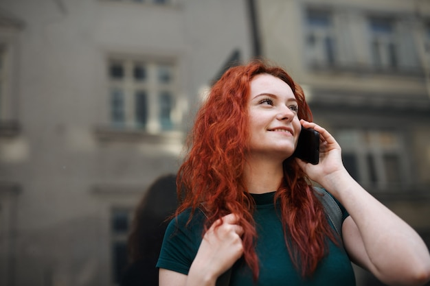 Un portrait de jeune femme avec sac à dos debout à l'extérieur dans la rue de la ville, à l'aide d'un smartphone.