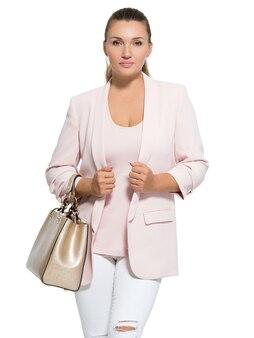 Portrait d'une jeune femme avec sac à main posant au studio