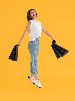 Portrait jeune femme avec des sacs à provisions sautant