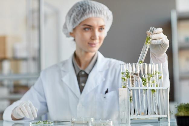 Portrait de jeune femme scientifique tenant un tube à essai avec des échantillons de plantes tout en travaillant sur la recherche en laboratoire de biotechnologie, copy space
