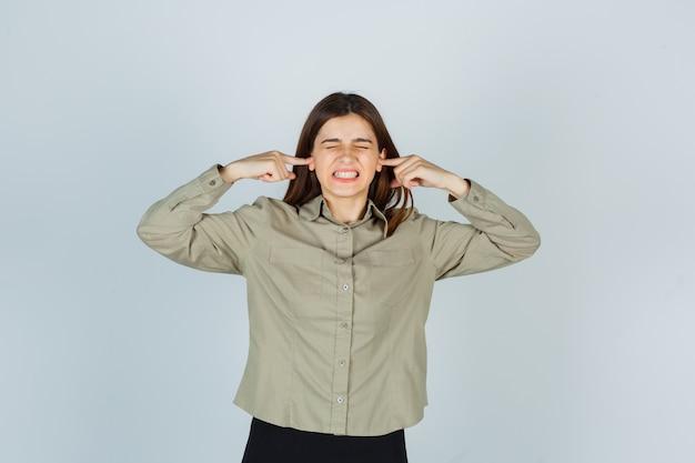 Portrait de jeune femme se branchant les oreilles avec les doigts en chemise, jupe et à la vue de face ennuyée