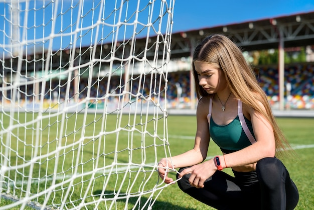 Portrait d'une jeune femme se reposant après avoir fait de l'exercice ou couru sur le stade. concept de remise en forme et de mode de vie sain