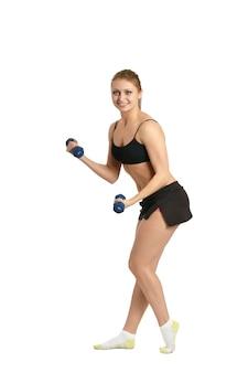 Portrait de jeune femme séance d'entraînement avec des haltères sur blanc