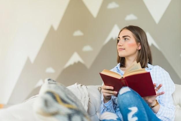 Portrait, jeune, femme, séance, sofa, tenue, livre