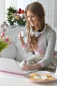 Portrait d'une jeune femme séduisante à l'aide d'un ordinateur portable