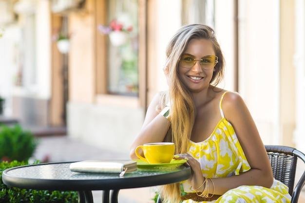 Portrait de jeune femme séduisante, assis au café avec une tasse de café. dame buvant du thé aromatique. photo de belle fille à la cafétéria en attendant son rendez-vous.