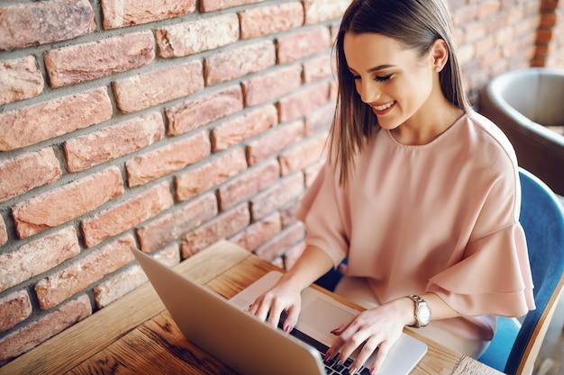 Portrait de jeune femme séduisante, assis dans la cafétéria et à l'aide d'un ordinateur portable