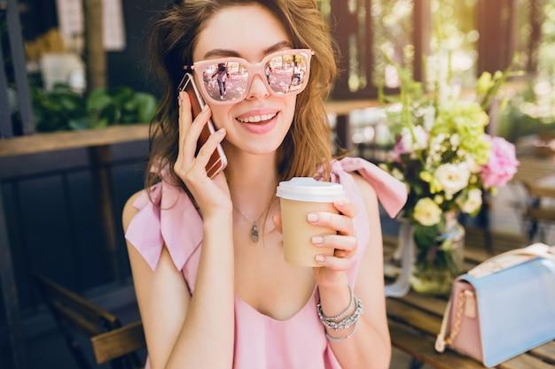 Portrait de jeune femme séduisante assise au café, tenue de mode d'été, robe en coton rose, lunettes de soleil, souriant, boire du café, accessoires élégants, vêtements à la mode, parler au téléphone