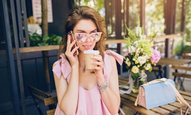 Portrait de jeune femme séduisante assise au café, tenue de mode d'été, style hipster, robe en coton rose, lunettes de soleil, souriant, boire du café, accessoires élégants, vêtements à la mode, parler au téléphone