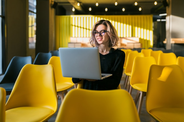 Portrait de jeune femme séduisante assise dans une salle de conférence travaillant sur un ordinateur portable portant des lunettes, l'apprentissage des élèves en classe avec de nombreuses chaises jaunes
