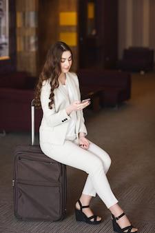 Portrait jeune femme séduisante assise sur des valises dans le terminal ou la gare. la fille s'est rencontrée lors d'un voyage.