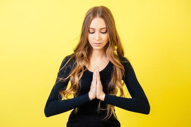 Portrait d'une jeune femme séduisante aux cheveux longs pratiquant le yoga et méditant en studio sur fond jaune. concept de tranquillité et de détente