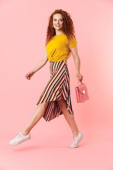 Portrait d'une jeune femme séduisante aux longs cheveux roux bouclés marchant isolé, portant un sac à main