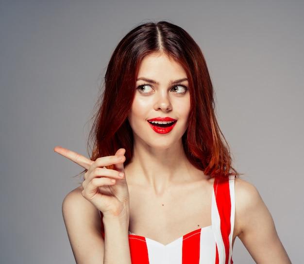 Portrait d'une jeune femme séduisante et belle avec des lèvres rouges, des cheveux rouges en vol