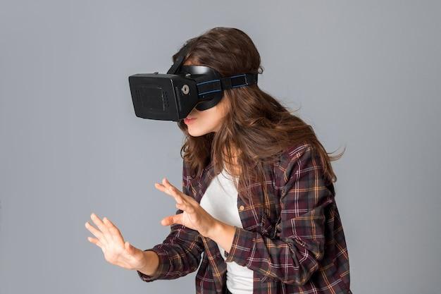 Portrait de jeune femme séduisante en casque de réalité virtuelle en studio sur mur gris