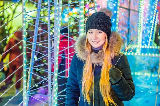 Portrait de jeune femme séduisante célébrant tenant des étincelles