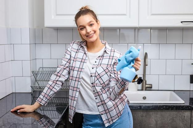 Portrait d'une jeune femme séduisante en chemise à carreaux tenant un chiffon et un détergent dans les mains après le nettoyage de la cuisine